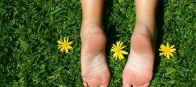 pies de mujer en cesped con flores